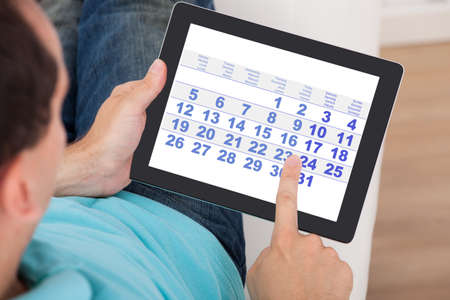 デジタル タブレットの自宅のカレンダーを使用している人のクローズ アップ