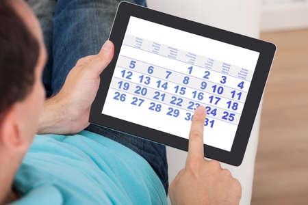 hombre caucasico: Primer plano de hombre usando el calendario en la tableta digital en el hogar Foto de archivo
