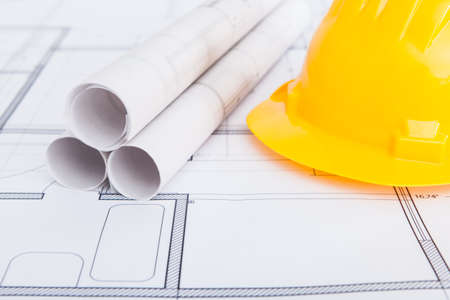 protection plan: Closeup photo of hard hat and blueprints