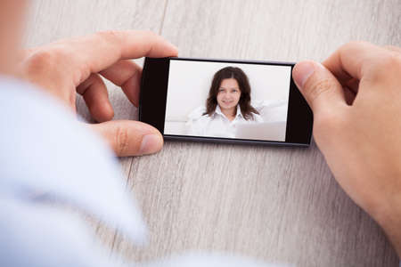 Cropped image of businessman chatting with female colleague through smartphone at office table photo