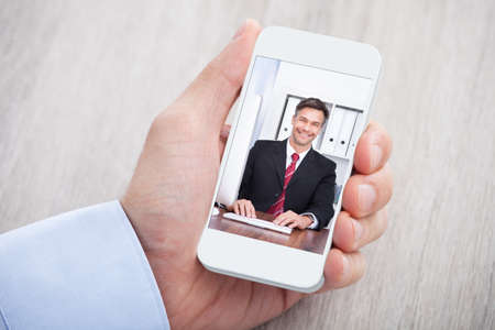Cropped image of businessman video conferencing with colleague at desk
