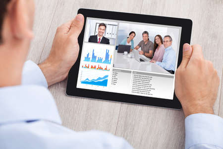 비즈니스맨: 사무실에서 책상에 디지털 태블릿에 팀과 함께 사업가 화상 회의의 자른 이미지 스톡 사진
