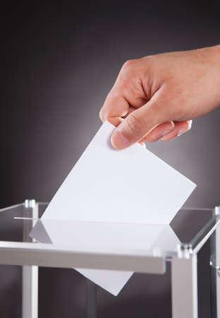 voting ballot: Cropped image of businessman inserting ballot in box on desk against black background