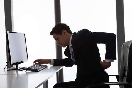 Side view of young businessman suffering from backache in office photo