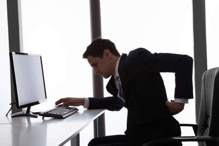 Zijaanzicht van jonge zakenman die lijden aan rugpijn in het kantoor