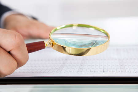 cropped image: Cropped image of businessman examining audit with magnifying glass at desk in office