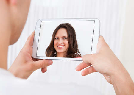 conferencing: Cropped image of man video conferencing with woman on digital tablet at home