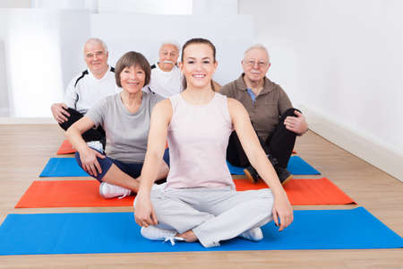 Portrait of confident trainer with senior customers sitting on exercise mat at gym photo
