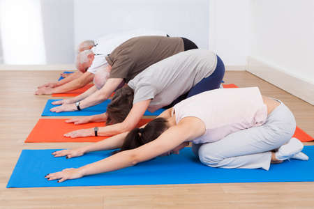 Row of people performing yoga on exercise mats at gym Stock Photo