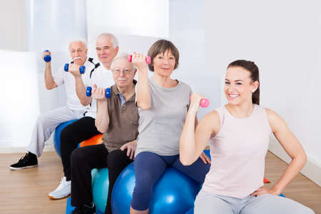people in a row: Portrait of trainer and senior customers using hand weights while sitting on fitness balls at gym