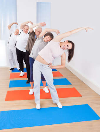 Full length portrait of happy trainer and senior customers doing stretching exercise at gym photo