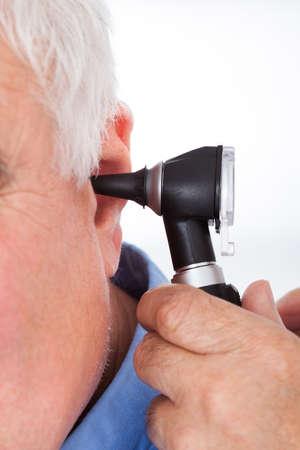 otoscope: Cropped image of doctor examining senior mans ear with otoscope against white background