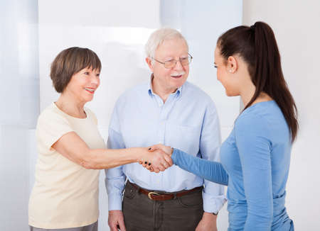 senior home: Young female caregiver shaking hands with senior couple at nursing home Stock Photo