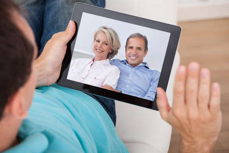 Cropped image of man having video chat with parents on digital tablet at home photo