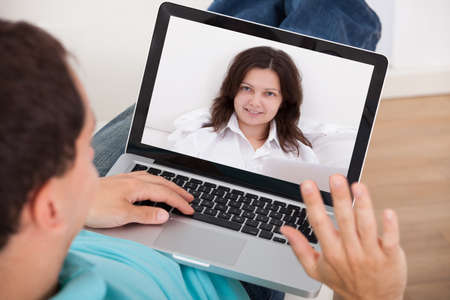 Man video conferencing with woman on laptop at home photo
