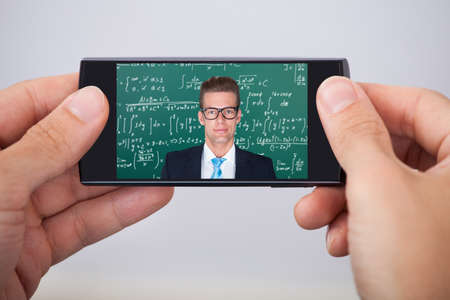 adult man: Mid adult man attending online maths lecture on smartphone Stock Photo