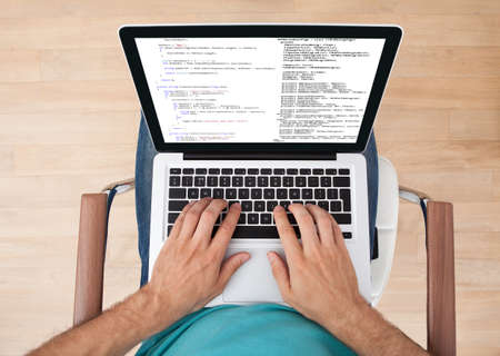 debugging: Directly above shot of mid adult man using laptop at home