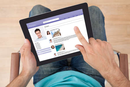 Directly above shot of man surfing on social site using digital tablet at home photo