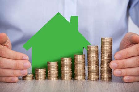 Sección media de manos del empresario de protección de las monedas de euro apiladas y modelo de la casa en la oficina Foto de archivo