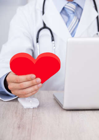 Midsection of male doctor holding red heart while using laptop at desk in clinic photo
