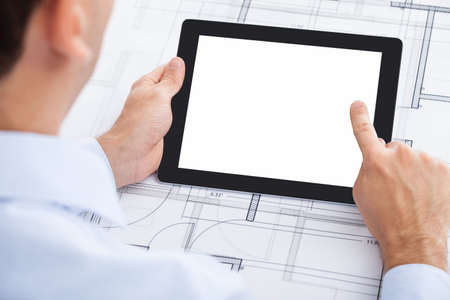 Cropped image of businessman holding blank digital tablet over blueprint in office photo