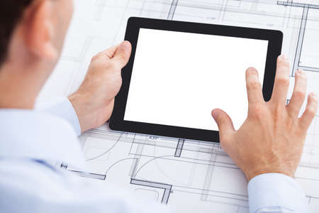 architect office: Cropped image of businessman holding blank digital tablet over blueprint in office Stock Photo