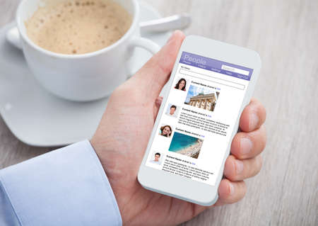 réseautage: Image recadrée d'affaires surfant sur le site de réseautage social sur téléphone mobile au bureau