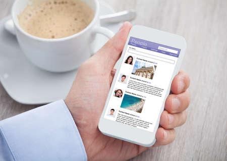 trabajo social: Recorta la imagen de hombre de negocios de surf sitio de redes sociales en el móvil en el escritorio de la oficina