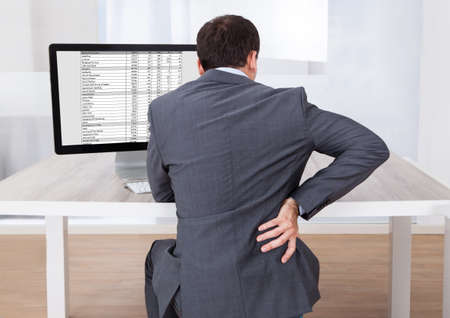sit: Rear view of businessman suffering from backache while sitting at computer desk in office