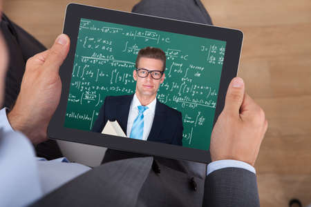 Midsection of businessman attending online maths lecture on digital tablet in office photo