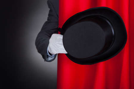 stage performer: Cropped image of magician holding hat behind stage curtain