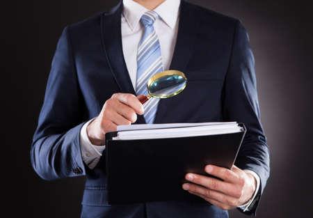 Buik van zakenman onderzoek van documenten met vergrootglas tegen zwarte achtergrond