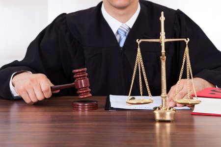 Buik van mannelijke rechter met hamer en weegschaal aan tafel in de rechtszaal Stockfoto