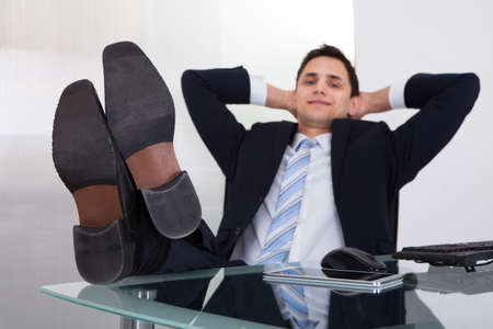 Full length of relaxed businessman daydreaming in office photo