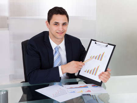 Portrait of confident businessman showing graphs at desk in office photo