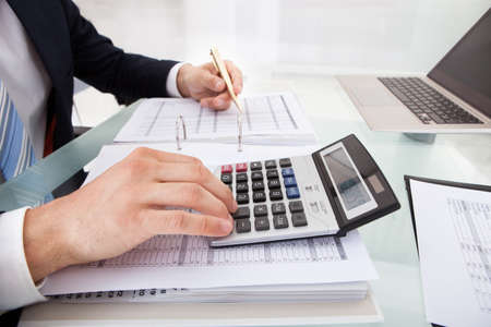 financial audit: Cropped image of businessman calculating expense at desk in office