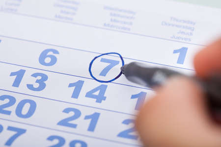 Cropped image of businessman marking date on calendar in office photo