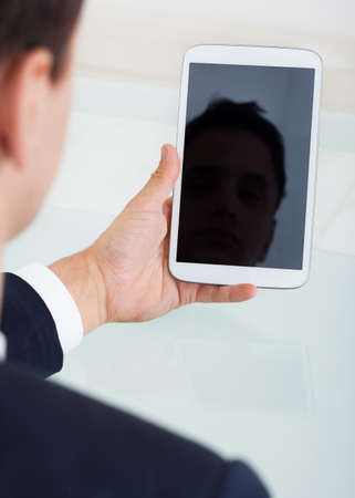 cropped image: Cropped image of businessman using digital tablet at desk in office Stock Photo