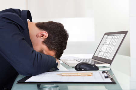 Side view of tired businessman sleeping while calculating expenses at desk in office photo