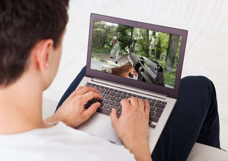 Midsection of young man playing action game on laptop at home photo