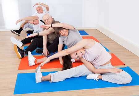 Portrait of smiling trainer and senior customers doing yoga at gym photo