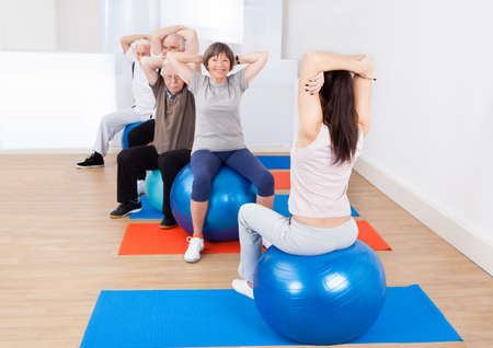 Rear view of female trainer training senior customers stretching on fitness balls in exercise class photo
