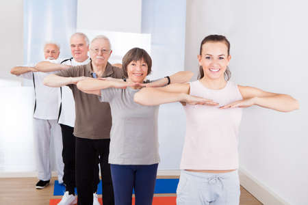 Portrait of happy trainer and senior customers exercising at gym photo