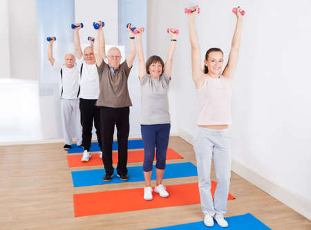 Full length portrait of trainer and senior customers lifting dumbbells at gym photo