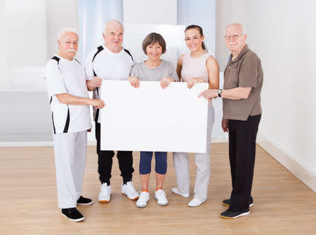 Full length portrait of trainer and senior customers holding blank billboard at healthclub photo