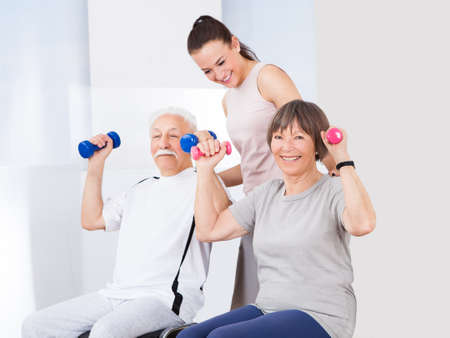 a young old couple: Young female trainer assisting senior couple with dumbbells at healthclub