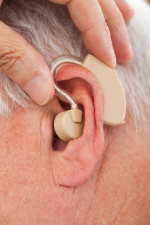 listening device: Cropped image of doctor inserting hearing aid in senior mans ear
