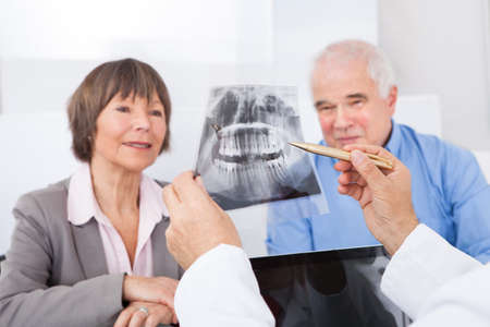 Man tandarts uitleggen tandheelkundige x-ray tot senior paar in kliniek