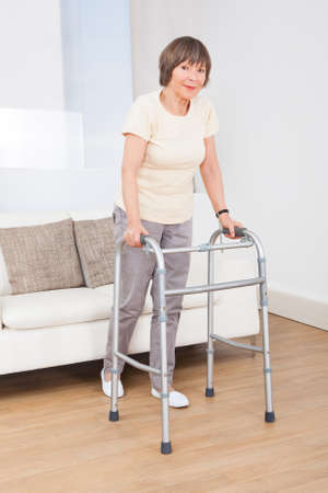 Full length portrait of senior woman using walking frame at nursing home