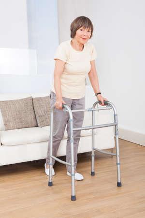 60s adult: Full length portrait of senior woman using walking frame at nursing home